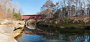 Narrows Covered Bridge was built in 1882 in Burr Arch style by J.A. Britton. Walk across this bridge in Turkey Run State Park, in historic Parke County, Indiana, USA. Sugar Creek reflects the covered bridge plus the concrete arch of the modern highway bridge seen behind. Panorama stitched from 6 photos.
