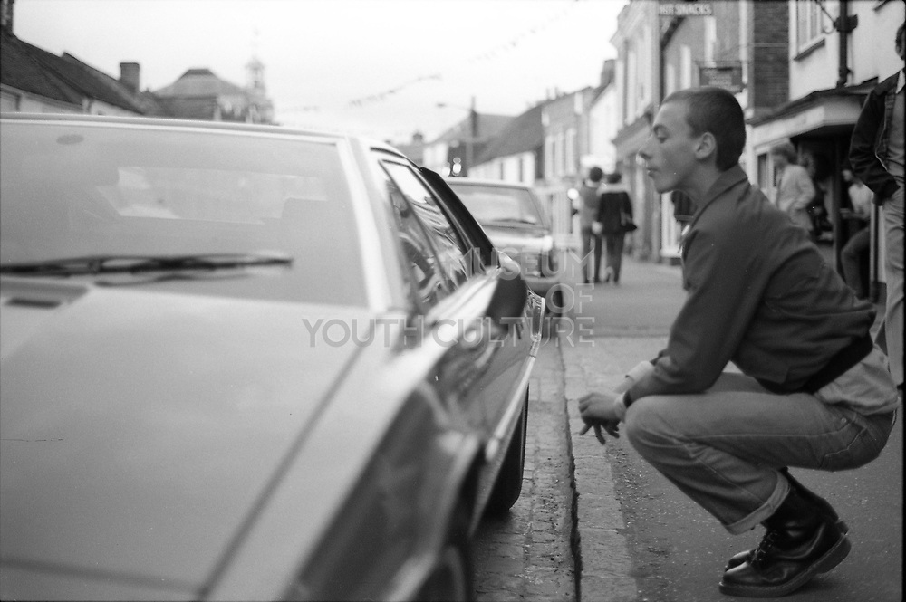 Symond looking into a car, High Wycombe, UK. 1980s.