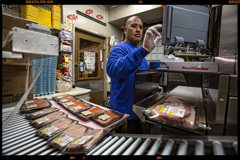 P.J. Augustiro, 41 Meat Dept. Supervisor for 26 years at Friendly Market gets prices on seafood and meats before they go out to the counter for sale.