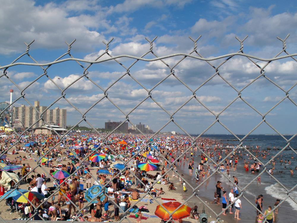 Coney Island Brooklyn New York USA Nordamerika Boardwalk Freizeit Vergnuegungspark Strand Menschenmenge Schirme Zaun