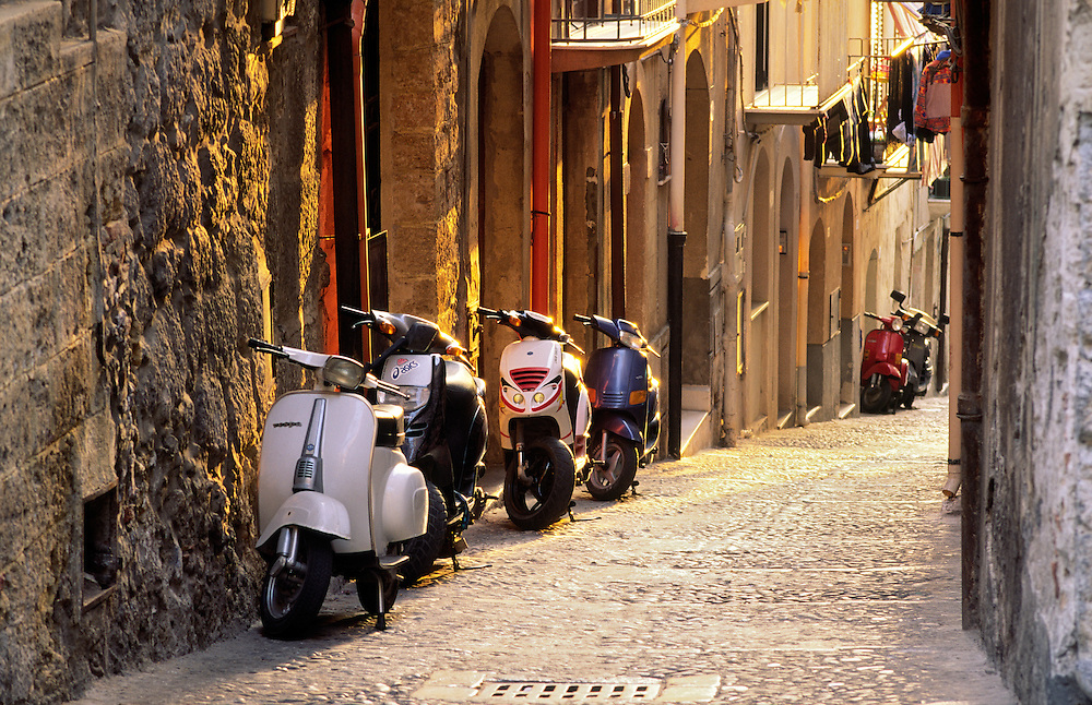 Cefalu, Sicily, Italy. Scooters, mopeds on cobbled street alleyway of coastal fishing resort town of Cefalu past. Evening