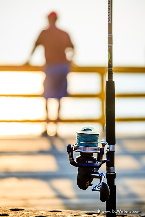 Fishing reel at Avalon pier on the NC coast.  I used a shallow depth of field to throw the fisherman in the background out of focus.