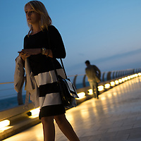 A women looks out on the Mediterranean as she walks near the Grimaldi Forum Monaco in Monte Carlo.