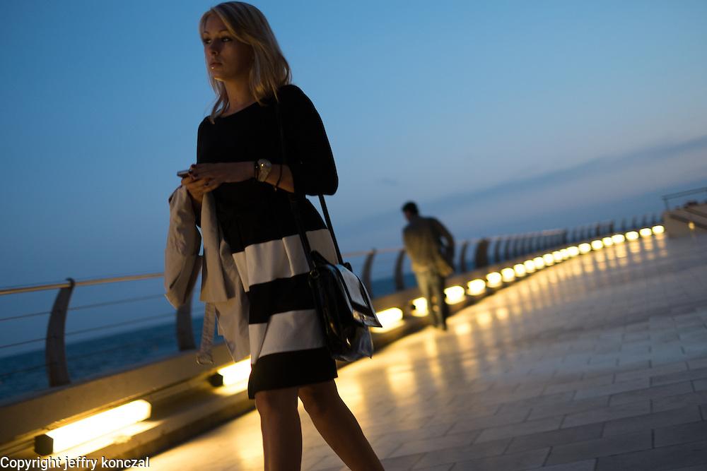 A women looks out on the Mediterranean as she walks near the Grimaldi Forum Monaco in Monte Carlo.