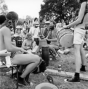 A crowd of people participating in a drum workshop along with other drummers and watchers, at Glastonbury, 1989.