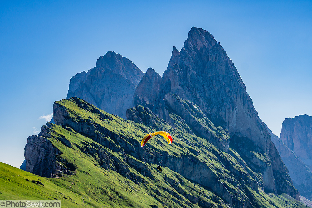 A paraglider glides over Alpe di Seceda and Val Gardena in the Geisler/Odle Group, in Trentino-Alto Adige/Südtirol (South Tyrol) region of Italy, in the Dolomites, part of the Southern Limestone Alps, Europe. For our favorite hike in the Dolomiti, start with the first morning bus from Selva to Ortisei, take the Seceda lift, admire the great views from the cross, then walk 12 miles (2000 feet up, 5000 feet down) via the steep pass Furcela Forces De Sieles (Forcella Forces de Sielles) to beautiful Vallunga (trail #2 to 16), finishing where you started in Selva. The hike traverses the Geisler/Odle and Puez Groups from verdant pastures to alpine pleasures, all preserved in a vast Nature Park: Parco Naturale Puez-Odle (German: Naturpark Puez-Geisler; Ladin: Parch Natural Pöz-Odles), including the deeply glaciated U-shaped valley of Vallunga (Langental). UNESCO honored the Dolomites as a natural World Heritage Site in 2009.