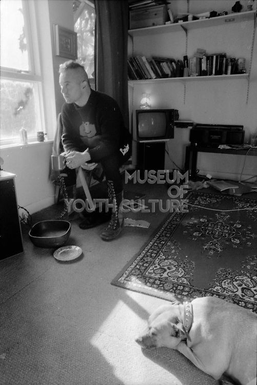 Thommo sat inside with dog, 1980s.