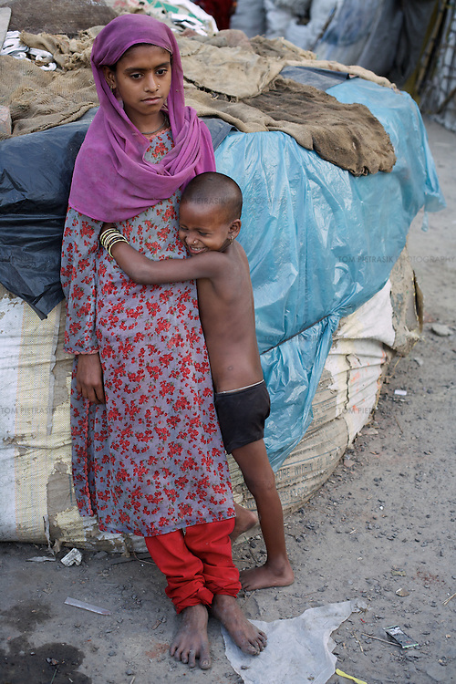 Sahera leans on a large rubbish sack worn out from work outside her home. Four year old sister Shazda holds onto Sahera. <br />
