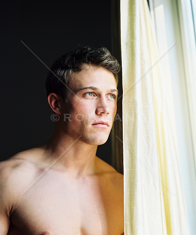 Shirtless young man standing  beside window curtains