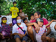 """22 JANUARY 2018 - CAMALIG, ALBAY, PHILIPPINES: People evacuated from their homes on the slopes of the Mayon volcano ride in a government truck to an evacuation center. There were a series of eruptions on the Mayon volcano near Legazpi Monday. The eruptions started Sunday night and continued through the day. At about midday the volcano sent a plume of ash and smoke towering over Camalig, the largest municipality near the volcano. The Philippine Institute of Volcanology and Seismology (PHIVOLCS) extended the six kilometer danger zone to eight kilometers and raised the alert level from three to four. This is the first time the alert level has been at four since 2009. A level four alert means a """"Hazardous Eruption is Imminent"""" and there is """"intense unrest"""" in the volcano. The Mayon volcano is the most active volcano in the Philippines. Sunday and Monday's eruptions caused ash falls in several communities but there were no known injuries.    PHOTO BY JACK KURTZ"""