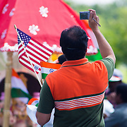 A man holding both the american and indian flag while photographing the colorful native costumes during the  Inaugural India Day Parade Saturday. August. 18, 2012. in Hockessin Delaware...Indian's around the world celebrates india's 65th anniversary of india's independence from British rule and the country's birth as a sovereign nation on August 15, 1947.