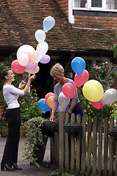 Longparish, near Andover. Richard Faulds got a gold medal in the shooting at the olympics. He lives in Longparish. Left to Right: Zoe Dale and Moon Hare, bar staff, put balloons outside his local pub The Plough Inn to celebrate his win, September 29, 2000. Photo by Andrew Parsons / i-Images..