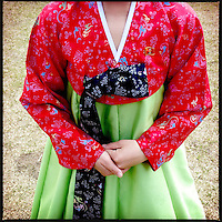 A woman in traditional Korean dress with a pin of Kim Il-sung on her breast, in Kaesong, North Korea.