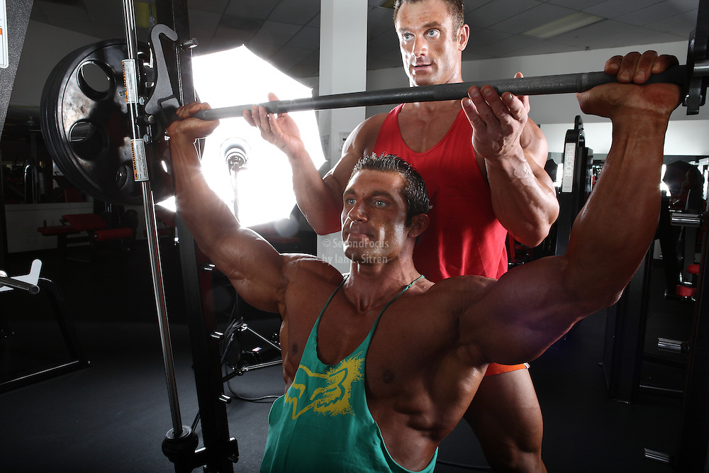 Bodybuilders Dan Decker and Brian Yersky doing shoulder presses on the Smith machine.
