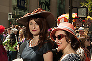 Two women wearing hats that harken to the 1940s.