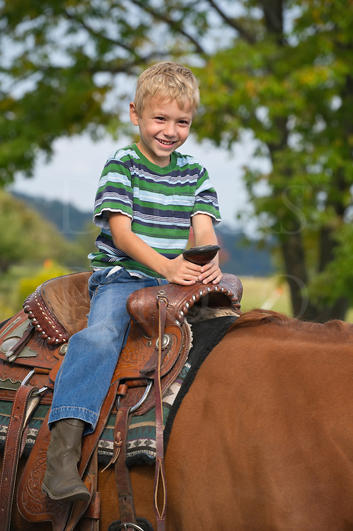 Young boy horseback riding on an adult saddle, a farm kid six years old enjoying himself smiling and happy, summer in Pennsylvania, USA.