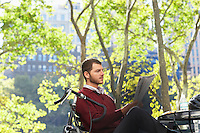 Man reading newspaper in park