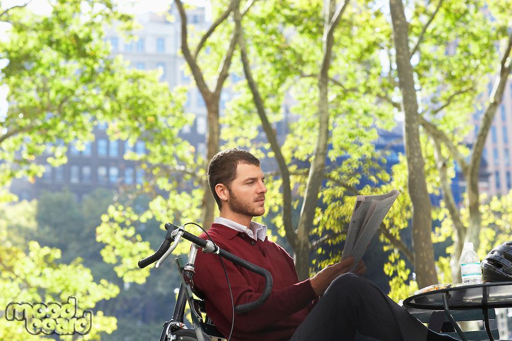 Man reading newspaper in park