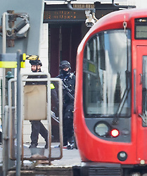 © Licensed to London News Pictures. 15/09/2017. London, UK. Armed police (L) can be seen next to the evacuated tube train at Parsons Green Station after a small explosion during the morning rush hour. A number of casualties have been reported. Photo credit: Peter Macdiarmid/LNP