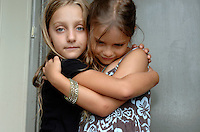 Two younng girlfriends hug each other.