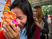 31 AUGUST 2014 - SARIKA, NAKHON NAYOK, THAILAND: A Thai woman holds a statue of Ganesh and prays at the Ganesh festival at Shri Utthayan Ganesha Temple in Sarika, Nakhon Nayok. Ganesh Chaturthi, also known as Vinayaka Chaturthi, is a Hindu festival dedicated to Lord Ganesh. It is a 10-day festival marking the birthday of Ganesh, who is widely worshiped for his auspicious beginnings. Ganesh is the patron of arts and sciences, the deity of intellect and wisdom -- identified by his elephant head. The holiday is celebrated for 10 days, in 2014, most Hindu temples will submerge their Ganesh shrines and deities on September 7. Wat Utthaya Ganesh in Nakhon Nayok province, is a Buddhist temple that venerates Ganesh, who is popular with Thai Buddhists. The temple draws both Buddhists and Hindus and celebrates the Ganesh holiday a week ahead of most other places.    PHOTO BY JACK KURTZ