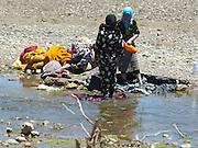 Women wash clothes in a river, Morocco