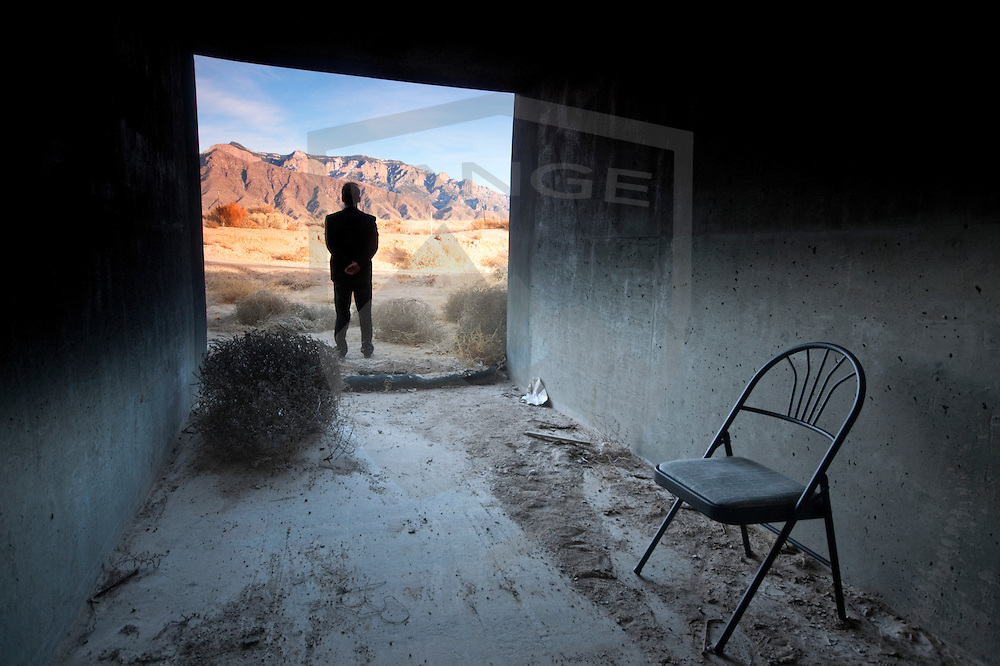man standing at the threshold of the landscape with chair in concrete enclosure.  sandia mountains, albuquerque, new mexico.