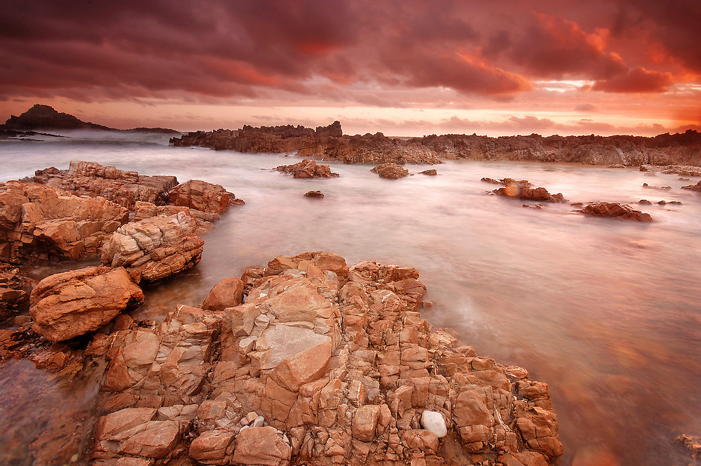 Once again, the rough and ready coastline of the Western Cape captured my imagination. A storm had just rumbled through the area and was lifting. The low clouds were moving quickly across the water, the sea was churned up and the sun was just peeking out after being obscured during the downpour. The light became a furious red and orange, I managed to get 4 images during this time, this was my favourite.