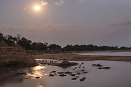 Impressionen aus dem South Luangwa NP im September gegen das Ende der Trockenzeit. Flusspferde beim Hide des Kaingo-Camps.<br /> <br /> Hippos im Pool bei Aufgang des Vollmonds zur Blauen Stunde.<br /> <br /> Das Flusspferd (Hippopotamus amphibius), auch Nilpferd oder Gro&szlig;flusspferd genannt, ist ein gro&szlig;es, pflanzenfressendes S&auml;ugetier. Es lebt in Gew&auml;ssern&auml;he im mittleren und s&uuml;dlichen Afrika und z&auml;hlt nach den Elefanten zu den schwersten landbewohnenden S&auml;ugetieren. Zusammen mit dem Zwergflusspferd und zahlreichen ausgestorbenen Arten bildet es die Familie der Flusspferde (Hippopotamidae). Traditionell werden diese in die Ordnung der Paarhufer gestellt; nach derzeitiger Lehrmeinung sind jedoch die Wale die n&auml;chsten Verwandten der Flusspferde, die zusammen mit den Paarhufern das Taxon der Cetartiodactyla bilden. Obwohl &bdquo;-pferd&ldquo; genannt, ist das Flusspferd mit den Pferden nicht verwandt. Mit einem Gesamtbestand von rund 125.000 bis 150.000 Tieren und einem erwarteten weiteren R&uuml;ckgang der Population z&auml;hlt es zu den gef&auml;hrdeten Arten.
