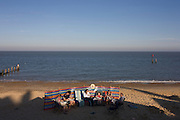 Beach family enjoy late sun in early evening at the Suffolk seaside town of Southwold, Suffolk.