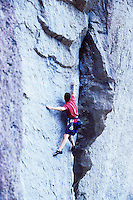 A young man rock climbing at Smith Rock State Park, Oregon, USA.