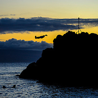 Cliff diver leaps off Black Rock at Kaanapali Beach during the nightly sunset ceremony