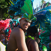A male dancer throws a dirty look back to a couple of female spectators. The Notting Hill Carnival has been running since 1966 and is every year attended by up to a million people. The carnival is a mix of amazing dance parades and street parties with a distinct Caribbean feel.