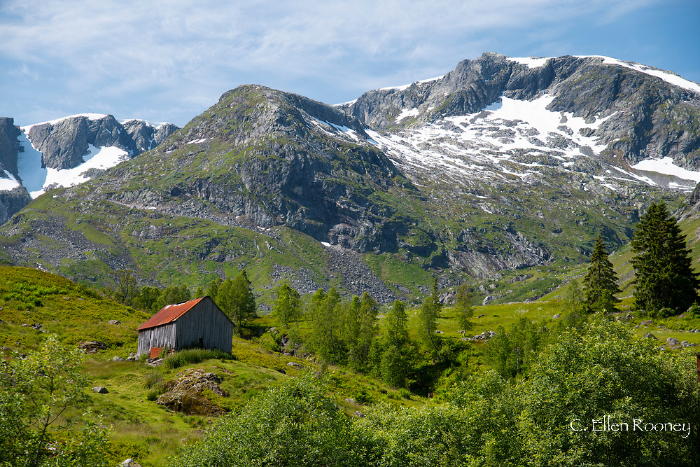 A wooden barn on a hillside below the Frudalsbreen Glacier, Vestlandet, Norway