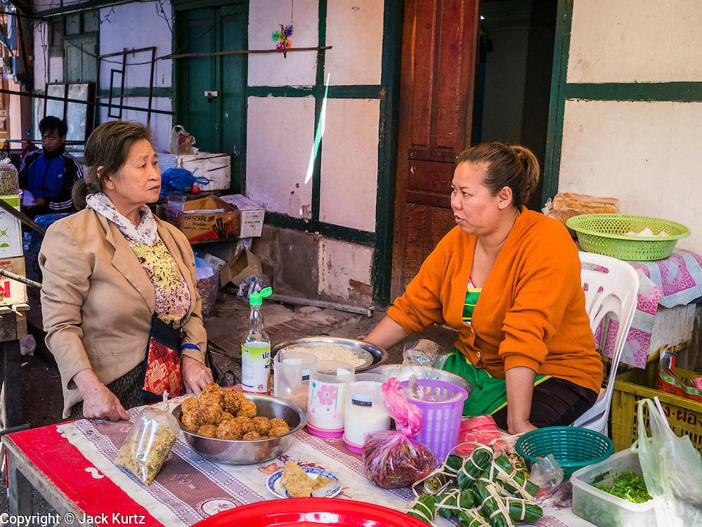 11 MARCH 2013 - LUANG PRABANG, LAOS: Women chat in the market in Luang Prabang, Laos.     PHOTO BY JACK KURTZ