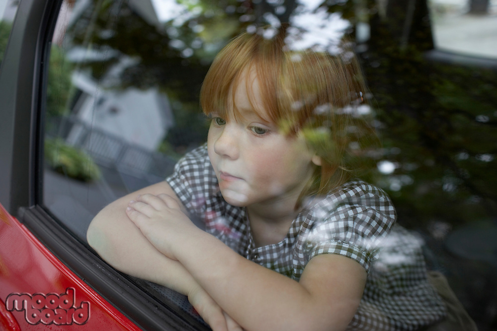 Pre-teen girl looking through car window and contemplating