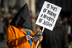 © Licensed to London News Pictures. 11/01/2017. London, UK. Demonstrators dress up as 'sad clowns' to campaign for the closure of Guantanamo Bay Prison, on the prison's 15th anniversary since opening. President-elect Donald Trump has called for no further releases from the prison, whilst President Obama was unable to follow his campaign promise to close the prison. Photo credit : Tom Nicholson/LNP