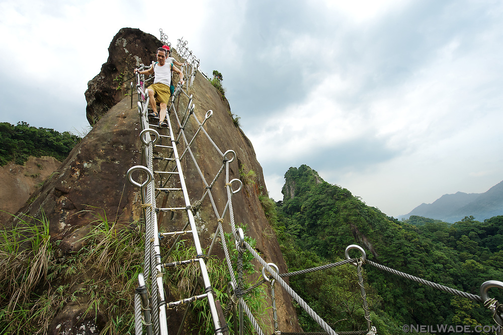 A couple of men descend from the peak of Xiaozi Shan (???) on a aluminum ladder in Pingxi (??), Taiwan.