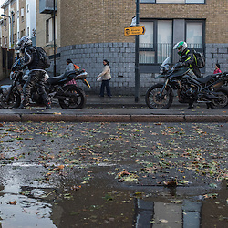 London, UK - 19 September 2014: motorbikers walk with thier motorbikes on wick Road as torrential rains cause floods and travel disruptions in East London