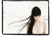 woman at the beach with her black hair flowing in the wind.