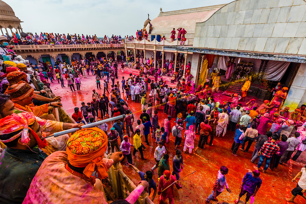 Filling squirters from vats of colored liquids that are sprayed on the crowd below, Lathmar Holi (Holi-the festival of colors), Nandgaon village, near Mathura, Uttar Pradesh, India.