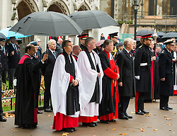 © Licensed to London News Pictures. 04/11/2015. London, UK. Clergymen stand underneath umbrellas during the service. A service to mark the opening of the Filed of Remembrance at Westminster Abbey, attended by Prince Philip, Duke of Edinburgh and Prince Harry.  The Field of remembrance is a memorial garden to commemorate British and Commonwealth military and civilian servicemen and women in the two World Wars and later conflicts. Photo credit: Ben Cawthra/LNP