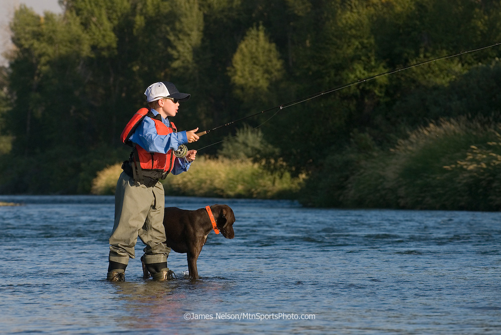A nine-year-old boy, with his German short-hair pointer, casts a fly for trout on the South Fork of the Snake River, Idaho.