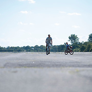 September 9, 2012 - Brooklyn, NY : Once New York City's municipal airport, Floyd Bennett Field is now administered by the Parks Department as a recreation site. The old runways remain -- providing ideal space to ride bikes and fly model airplanes.  Pictured here, Dante Lopez, left, and his five-year-old son Carlos ride bicycles on Sunday afternoon. Dante expressed that Floyd Bennett Field, with its wide open spaces devoid of vehicular traffic, is the ideal place for inexperienced riders like Carlos, who just learned to ride his bicycle two weeks ago. CREDIT: Karsten Moran for The New York Times