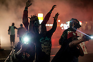 A group of protesters dance and take photos in the lingering smoke on West Florissant Ave. Protests have been ongoing in Ferguson, Missouri since the shooting death of Michael Brown, the eighteen-year-old unarmed teen killed by police on August 9, 2014.