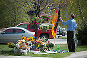 On May 2, 2104, an unidentified neighbor and friend of the host family of Diren Dede, a German exchange student who was shot and killed by another neighbor, straightens a German flag that is part of a memorial for the student in the Grant Creek neighborhood of Missoula, Montana.