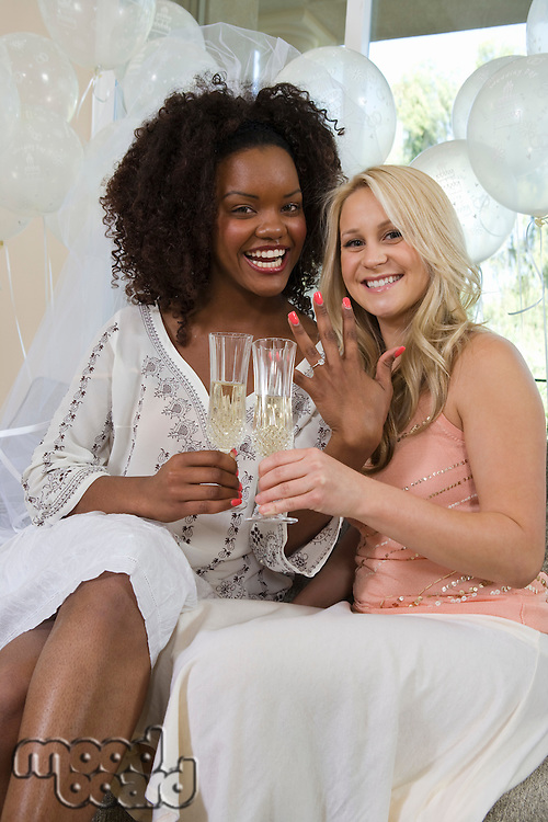 Young woman showing her engagement ring at bridal shower