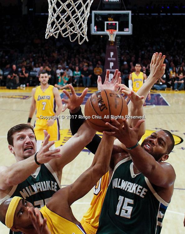 3月17日,洛杉矶湖人队球员欧米尔-阿西克(左下)与密尔沃基雄鹿队球员米尔扎-泰莱托维奇 (左) 和格雷格-门罗 (右) 在比賽中争抢篮板球。 当日,在2016-2017赛季NBA常规赛中,洛杉矶湖人队主场以103比107不敌密尔沃基雄鹿队。 新华社发 (赵汉荣摄)<br /> Los Angeles Lakers and Milwaukee Bucks vie for a ball during an NBA basketball game, Friday, March 17, 2017.(Photo by Ringo Chiu/PHOTOFORMULA.com)<br /> <br /> Usage Notes: This content is intended for editorial use only. For other uses, additional clearances may be required.