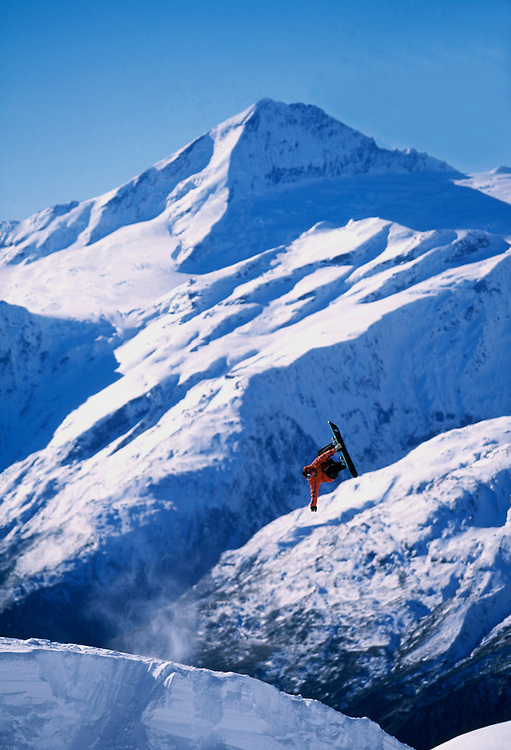 Snowboarder flying off a kicker at the Heli-Challenge in New Zealand with Mount Aspiring in the distance.pic: Mike Truelove