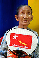An elderly woman refreshes from the extreme heat with a fan decorated with the NLD flag. Yangon, Myanmar. 2012